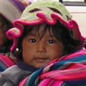 Wide-eyed Child Looking from Mother's Shawl